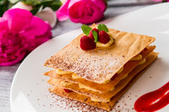 Pastry with raspberries on plate. Pink flowers and mint leaves. Millefeuille with decoration. Crispy dough and juicy berries Stock Photos