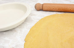 Pastry rolled out with rolling pin next to pie dish Stock Photography