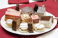 Pastry rows / savories cuts. Pastry rows /savories cuts on teller, table. Cream cake, punch cuts, liqueur spike Stock Photo