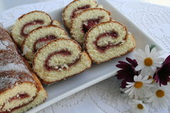 Pastry - rulltarta. Cake with raspberry jam on white plate with decoration of flower beside Stock Photos