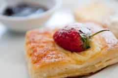 Pastry with strawberry. Delicious pastry with strawberry on top and jam in the background Stock Photos