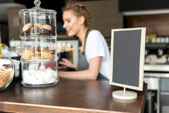 Pastry and tablet situating on desk. Focus on close up cookies in vases and menu board locating on table in confectionary shop. Waitress is working on background Royalty Free Stock Images