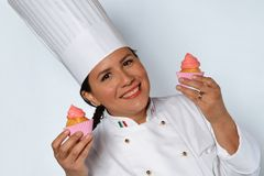 Pastry woman cook. Holding two creamy cup cakes Royalty Free Stock Images