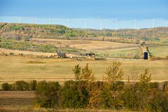 Pastures in fall with farm and wind turbines Royalty Free Stock Photo