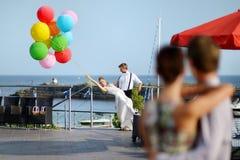 Państwo młodzi z kolorowymi balonami Obrazy Stock