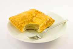 Pasty on Plate with Fork. Golden chicken pasty on a white plate with fork on a white background Stock Photo