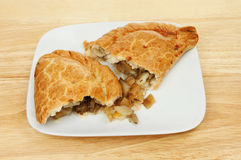 Pasty on a plate. Thw halves of a Cornish pasty on a plate on a wooden tabletop Stock Photo