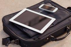 Pastylka i telefon komórkowy na modnej torbie kosmos kopii przewyższa Zdjęcie Stock