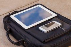 Pastylka i telefon komórkowy na modnej torbie kosmos kopii przewyższa Fotografia Royalty Free