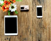Pastylka, kamera, telefon i kwiaty w wazie na starym drewno stole, Obrazy Royalty Free