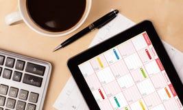 Pastylka komputer osobisty pokazuje kalendarz na ekranie z filiżanką kawy na d Obraz Stock