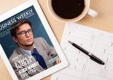 Pastylka komputer osobisty pokazuje magazyn na ekranie z filiżanką kawy na d Obraz Royalty Free