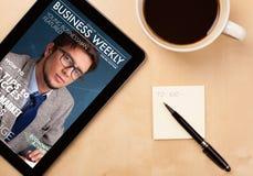 Pastylka komputer osobisty pokazuje magazyn na ekranie z filiżanką kawy na d Fotografia Stock