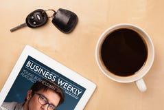 Pastylka komputer osobisty pokazuje magazyn na ekranie z filiżanką kawy na d Obrazy Stock
