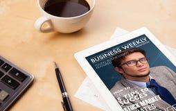 Pastylka komputer osobisty pokazuje magazyn na ekranie z filiżanką kawy na d Zdjęcie Stock