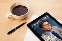 Pastylka komputer osobisty pokazuje magazyn na ekranie z filiżanką kawy na d Zdjęcia Stock