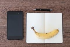 Pastylka, notatnik, pióro i banan na drewnianym stole, Wizerunek conc zdjęcie royalty free