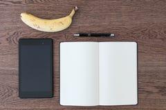 Pastylka, notatnik, pióro i banan na drewnianym stole, Wizerunek conc obrazy stock