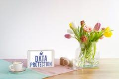 Pastylka z dane ochrony writing na drewnianym biurku z białymi półdupkami obraz stock