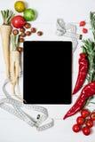 Pastylka z pomiarową taśmą, rozmarynami, korzeniem, czereśniowymi pomidorami, pieprzami i dokrętkami na białego rocznika drewnian zdjęcie stock