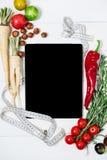 Pastylka z pomiarową taśmą, rozmarynami, korzeniem, czereśniowymi pomidorami, pieprzami i dokrętkami na białego rocznika drewnian fotografia stock