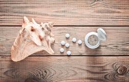 Pastylki wapnie i skorupa na drewnianym stole MEDYCZNY pojęcie Kopaliny dla zdrowie Zdjęcie Stock