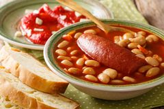 Pasulj grah bean soup with sausage is served with bread and be. Ll pepper close-up on a plate on the table. horizontal stock photo