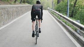Pasvorm geconcentreerde fietser pedaling fiets uit het zadel bergop Sterke benen met spieren het pedaling Bergopwaartse opleiding stock footage