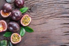 Pasyjne owoc i swój przekrój poprzeczny z papkowatym sokiem wypełniali z ziarnami Drewniany tło obrazy stock