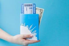 Paszport, dolary i lotniczy bilet w kobiety ręce na błękitnym tle, Podr??y poj?cie, kopii przestrze? fotografia stock