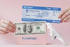 Paszport, dolary i lotniczy bilet w kobiety r?ce na r??owym tle, Podr??y poj?cie, kopii przestrze? zdjęcia stock