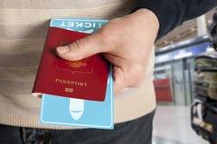 Paszport i bilet w ręce w lotnisku Zdjęcia Royalty Free