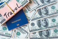Paszport i stos dolarowi banknoty z podpisem Podróżujemy na pieniądze tle obraz royalty free