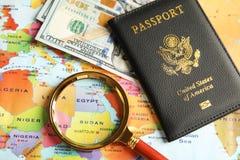 Paszport, pieniądze i magnifier na światowej mapie, obrazy stock