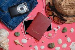 Paszport, Smartphone, Odziewa, okulary przeciwsłoneczni, fotografii kamera, Brown kapelusz na Różowym tle, Odgórnego widoku podró Fotografia Stock