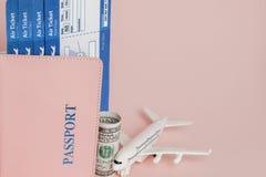 Paszporta, dolar?w, p?askiego i lotniczego bilet na r??owym tle, Podr??y poj?cie, kopii przestrze? obrazy royalty free