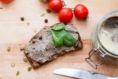 Patè sul pane con le foglie ed i pomodori del basilico Fotografie Stock