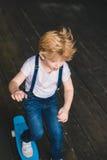 Patín del niño pequeño en el monopatín Imágenes de archivo libres de regalías