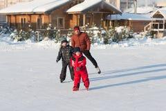 Patín feliz de la familia en el invierno Imagenes de archivo
