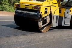 Patín pesado grande que pega un nuevo asfalto en el carril del camino imagenes de archivo