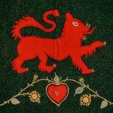 A pata vermelha do leão aumentou no tapete esperto de restos da tela imagens de stock