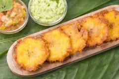 Patacon eller toston stekte och slätade stycken av grön pisang, traditionellt mellanmål eller ackompanjemang i det karibiskt, gua arkivbilder