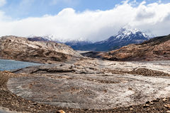 Patagonia Argentina. A lake, the dry rocky soil and the mountains with snow peaks Stock Photo