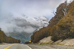 Patagonian Highway, Los Lagos, Chile. Highway surrounded by forest and snowy mountain at chilean patagonian territory royalty free stock images