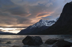 Patagonian sunset over lago nordenskjöld, Torres del Paine. Shooting the patagonian sunset with long exposure freezing the water and giving the clouds royalty free stock photos
