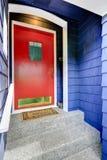 Patamar da entrada com a porta vermelha brilhante Fotografia de Stock