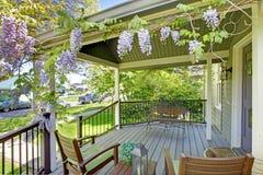 Patamar dianteiro da casa com cadeiras e flores. fotos de stock royalty free