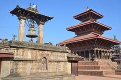 Patan,尼泊尔, 2012年10月, 26日,尼泊尔场面:走在古老Durbar方形的近的礼节响铃和himdu寺庙的人们 免版税库存图片