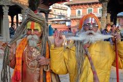 PATAN,尼泊尔- 2014年12月21日:两个Sadhus圣洁者画象Durbar广场的 免版税库存图片