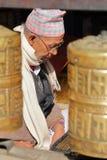 PATAN, НЕПАЛ - 19-ОЕ ДЕКАБРЯ 2014: Молитвы Bhudist непальского человека читая на золотом виске с колесами молитве на переднем пла Стоковые Изображения RF